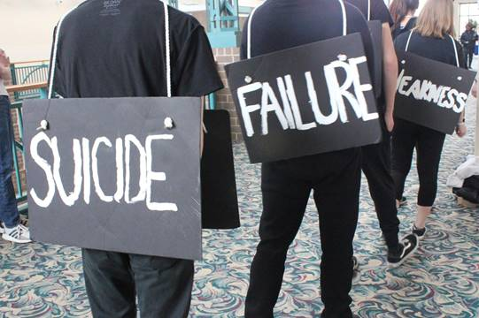 QCYC staff walking in a line, dressed in black and wearing signs that say 'Suicide', 'Failure', 'Weakness'