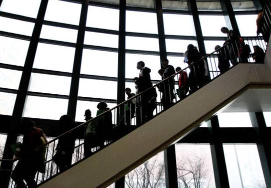 People descending a staircase with bright windows behind them
