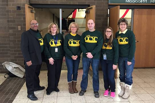QCYC staff members wearing dark green sweaters and jeans