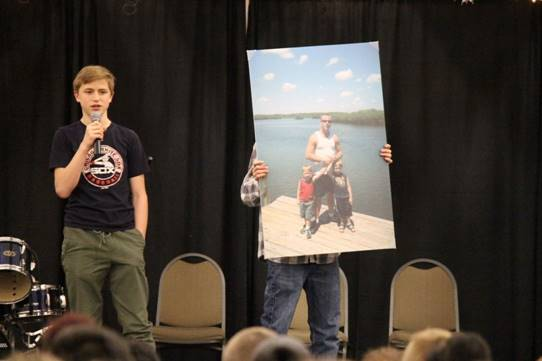Boy in black with microphone speaking to audience while person in plaid shirt holds up a picture of he, his brother, and his father