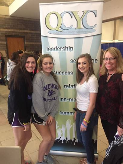 Girls standing in front of a QCYC poster